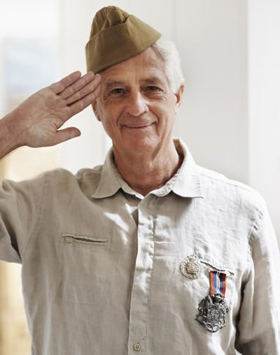A senior war veteran looking at the camera wearing his uniform