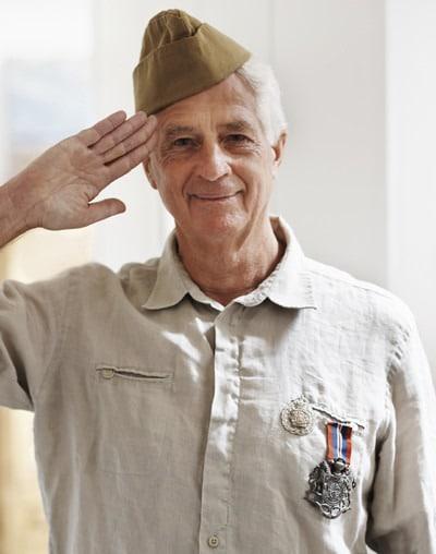 A senior war veteran looking at the camera wearing his uniform